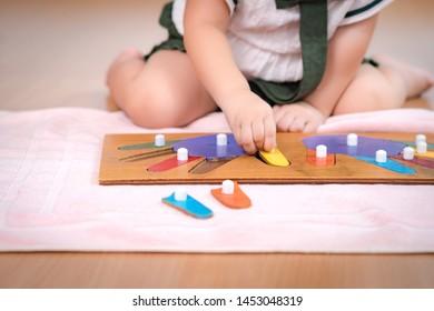 Closeup: Hands of a preschool little girl 2-3 years in Montessori classroom engaged sensory wooden puzzle activity. 10 fingers, Fine motor skills, Montessori method, Tools, Child development concept.