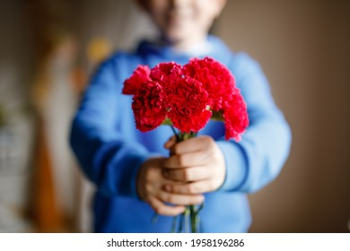 Closeup of hands of preteen kid boy holding bunch of clove flowers. Child congrats and presents cloves to mother or girl friend for mothers day or valentines day.