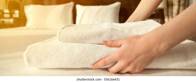 Close-up of hands putting stack of fresh white bath towels on the bed sheet. Room service maid cleaning hotel room. Lens flair in sunlight. Horizontal photo banner for website header design