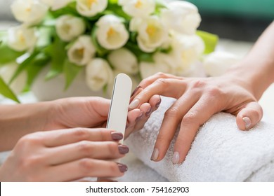 Close-up of the hands of a qualified manicurist filing the nails of a young woman with a white buffer in a trendy nail salon