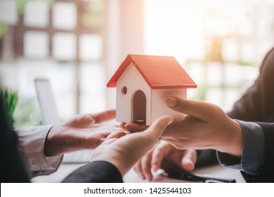 Closeup hands of real estate agent give house model to home ownership for young couple. Business successful contract concept.