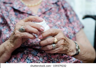 Close-up hands of senior woman taking pill