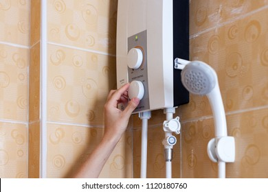 Close-up of hands setting the temperature of water in electric boiler in the shower room