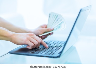 Close-up of hands shopping/paying online using laptop while holding US dollars..
