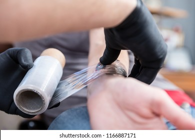 Close-up of the hands of a skilled tattoo artist wearing sterile black gloves while wrapping the forearm of a tattooed client