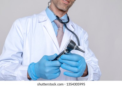 Close-up of the hands of a smiling doctor wearing a blue coat and gloves holding medical instruments and a device to look at the ears. medicine concept