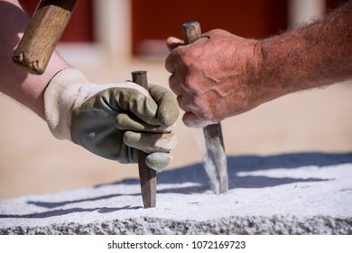 Closeup of the hands of a stonemason, hitting the stone