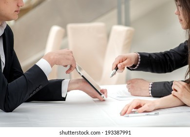 Close-up of hands with tablet and laptop. Businessmen on corporate meeting. Hands of young people at the table
