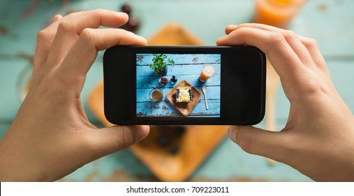 Close-up of hands taking photo of breakfast with mobile phone