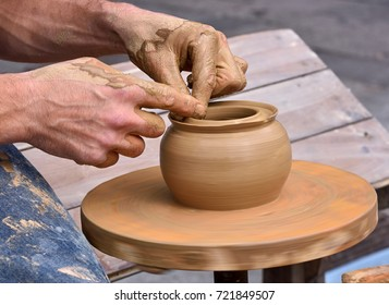 Close-up of hands that made a bowl turning a stoves on a potter's wheel