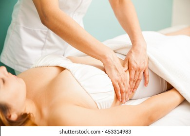 Closeup of the hands of a therapist giving a deep tissue massage to a female client at a spa