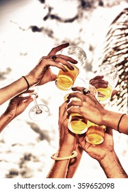 Closeup of hands toasting with glasses of beer.