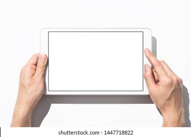 Closeup of hands touching white tablet computer on white background with shadow. Blank screen. Top view.