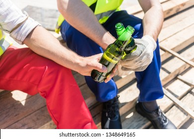Close-up of the hands of two blue-collar workers, toasting with bottles of cold beer during break on the construction site in a sunny day of summer