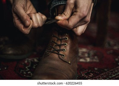 Closeup of  hands tying the laces of  his brown leather boots.