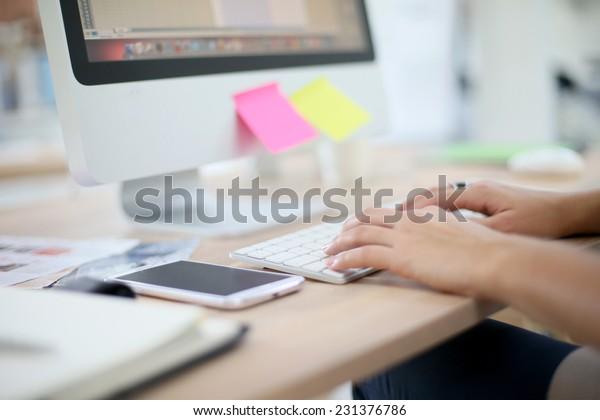 Closeup of hands typing on desktop keyboard