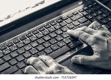 Closeup of hands typing on laptop with dark screen ove desk
