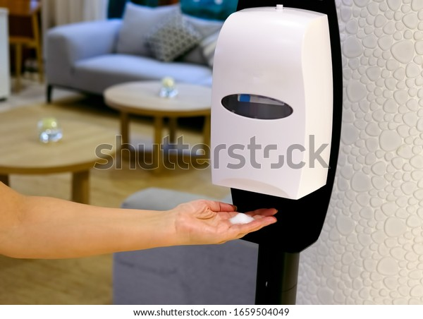 Closeup of Hands under the automatic alcohol dispenser. Sanitation station for cleaning of hands. Infection prevention concept. Selective focus closeup.