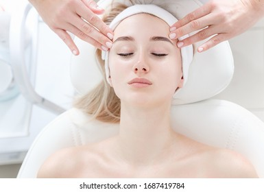 Close-up hands of an unidentified young woman masseur doing facial massage to beautiful young caucasian client girl at spa salon. Concept of therapeutic anti-aging skin tightening facial treatments