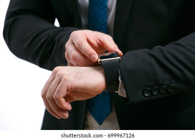 Close-up of hands of an unknown man in business suit with smart watch in the studio on a white isolated background