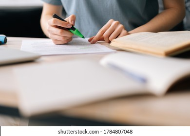 Close-up of hands of unrecognizable businesswoman highlighting important things in paper document with marker. Business lady working at home office.