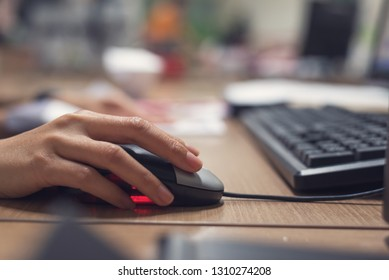 Closeup of  hands using computer mouse with computer Desktop PC at table.
