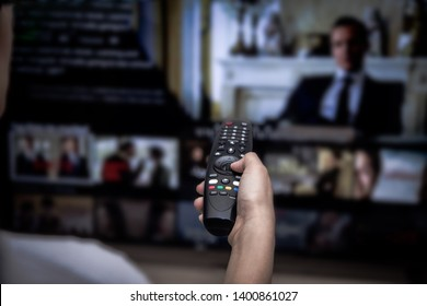 Close-up of hands using remote smart tv on blurred smart tv with video on demand as background