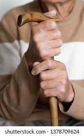 Closeup of the hands of a very elderly person in a beige sweater, health concept