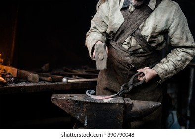 closeup hands of the village smithy, pulling the metallic article.