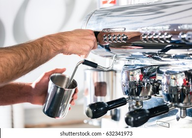 Close-up of the hands of a waiter preparing espresso at an automatic coffee machine