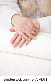 Closeup of the hands of a woman with manicured finger nails resting her hands over a rolled white towel in a beauty salon with copyspace