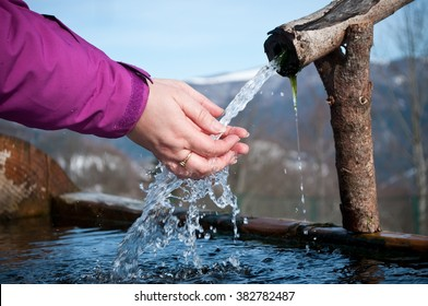 closeup of hands of woman in the natural fountain on mountain