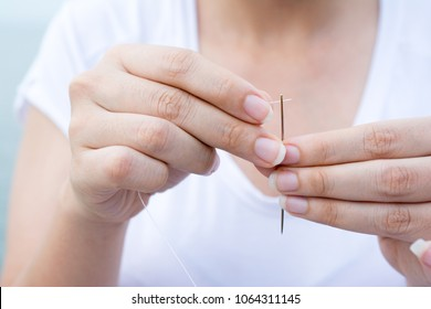 Close-up hand's of a woman tailor who puts thread in the needle. A symbol of fashion and professionalism.