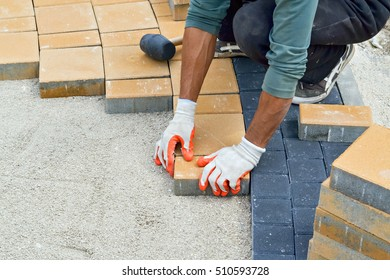 Closeup of the hands of a worker during paving the sidewalk