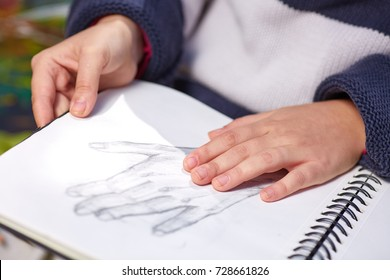 Close-up of the hands of young and beautiful artist