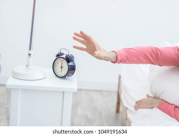 Closeup hands young man pressing snooze button on early morning digital alarm clock radio,  shallow depth of field focus on foreground