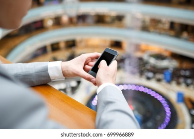 Close-up -  hands of young successful man typing in  smart phone in search of media materials against  backdrop of large blurred shopping center