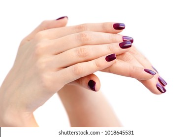 Closeup of hands of a young woman with dark red manicure on nails against white background