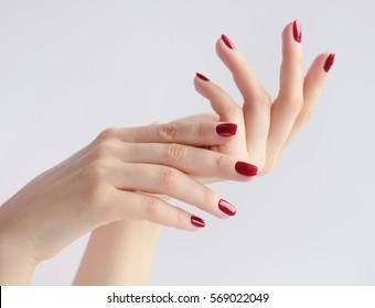 Nahaufnahme von Händen einer jungen Frau mit dunkelroter Maniküre auf Nägeln auf weißem Hintergrund