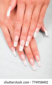 Closeup of hands of a young woman with french manicure on nails against white background