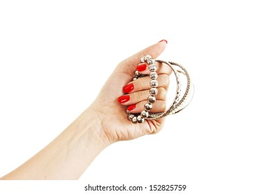 Closeup hands of young woman with red manicure polished nails holding many silver bangles. Isolated on white background.