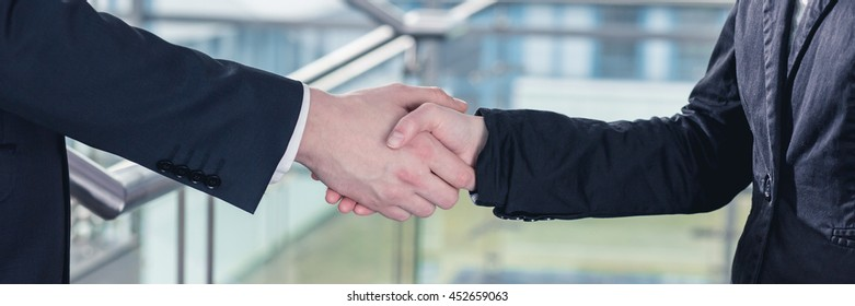 Close-up of handshake between two businesspeople after successful meeting
