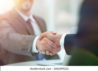 closeup .handshake of business partners above the Desk