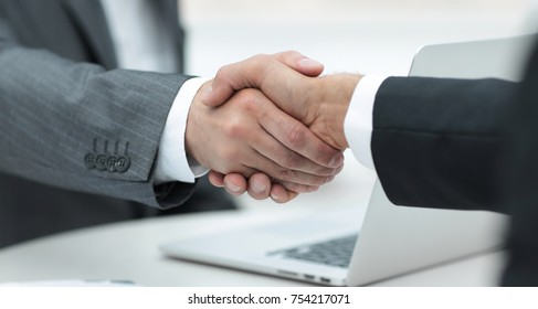 closeup .handshake of business partners above the Desk.the concept of partnership