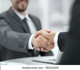closeup .handshake of business partners above the Desk