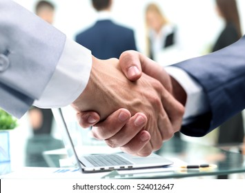 closeup of handshake of businessmen on background of the workpla