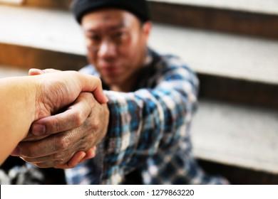 Close-up handshake homeless man on walkway street in the city.