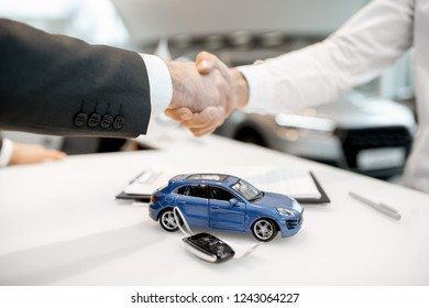 Close-up of a handshake at the table with toy car and keys. Car buying concept