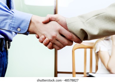 Close-up of a handshake of two businesspeople at the office.