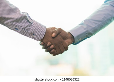 Closeup of handshake. Unrecognizable men in formal shirts closing deal and shaking hands. Partnership concept